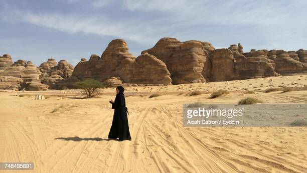 side view of woman in burka standing on desert during sunny day - 宗教的なベール ストックフォトと画像