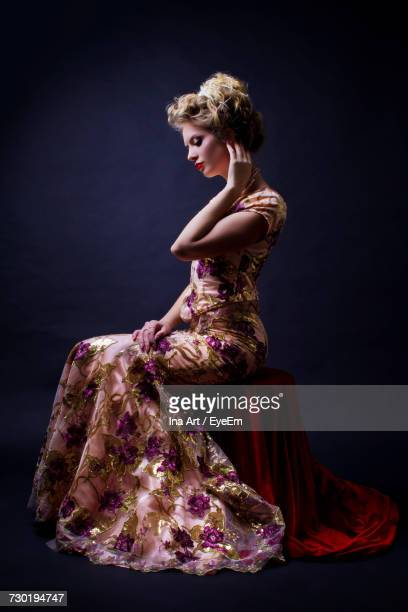 side view of woman in evening gown sitting against black background - evening gown stock pictures, royalty-free photos & images