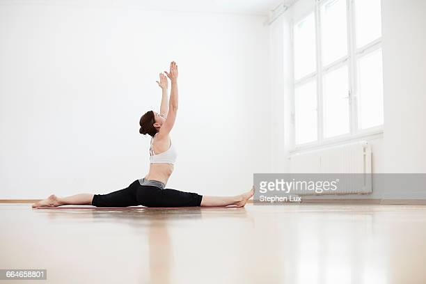 Side view of woman in exercise arms raised doing the splits