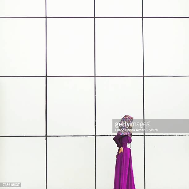 Side View Of Woman In Hijab Standing By White Wall