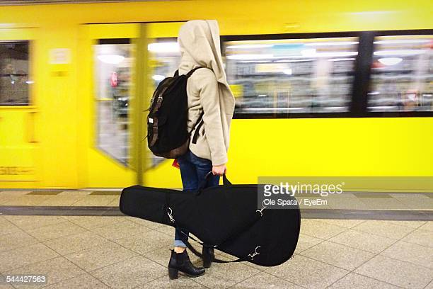 side view of woman in hooded jacket holding guitar while waiting at railway station - guitar case stock pictures, royalty-free photos & images
