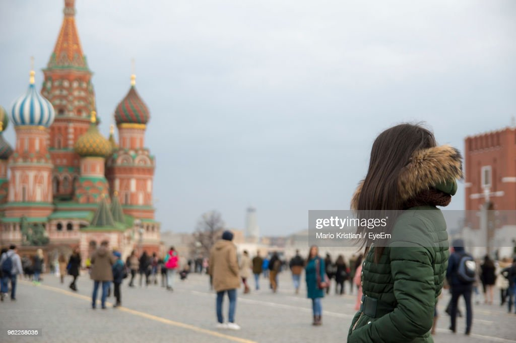 Side View Of Woman In Jacket Standing Against St Basil Cathedral : Stock Photo