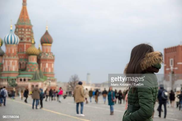 side view of woman in jacket standing against st basil cathedral - orthodox church stock pictures, royalty-free photos & images