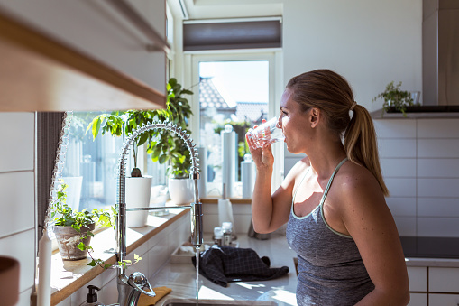 Side view of woman in sports clothing drinking water at kitchen - gettyimageskorea