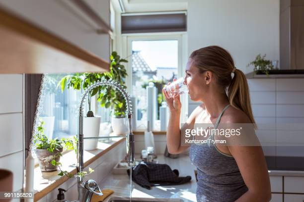 side view of woman in sports clothing drinking water at kitchen - drink water stock pictures, royalty-free photos & images
