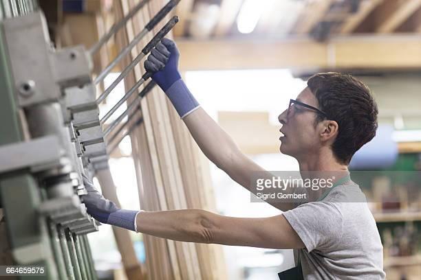 side view of woman in workshop pulling lever - sigrid gombert stockfoto's en -beelden