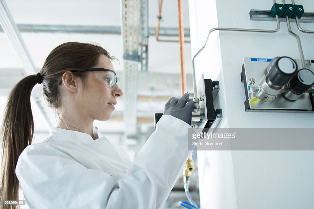 Side view of woman in workshop wearing safety goggles and coat adjusting control panel : Stock-Foto