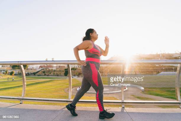 side view of woman jogging on elevated walkway against clear sky - voluptuous stock pictures, royalty-free photos & images