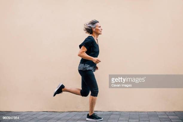 side view of woman jogging on footpath against wall - older woman stock pictures, royalty-free photos & images