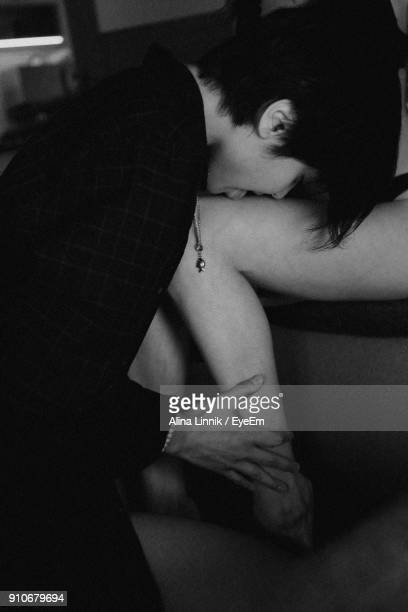 side view of woman kissing girlfriend leg - leg kissing stock photos and pictures