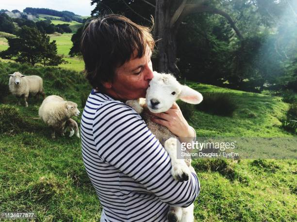 Side View Of Woman Kissing Lamb While Standing On Grassy Landscape