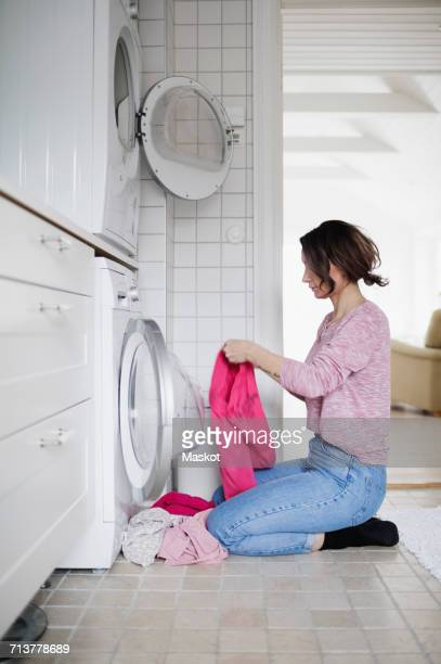 Side view of woman kneeling while loading clothes in washing machine