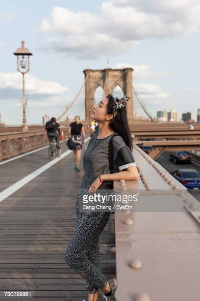 Side View Of Woman Leaning On Railing At Brooklyn Bridge