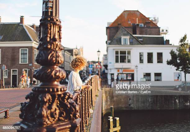 side view of woman leaning on railing by lake - haarlem stock photos and pictures