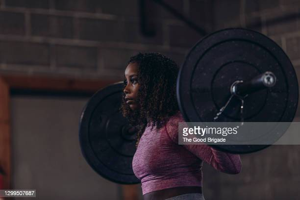 side view of woman lifting barbell in gym - women's weightlifting stock pictures, royalty-free photos & images