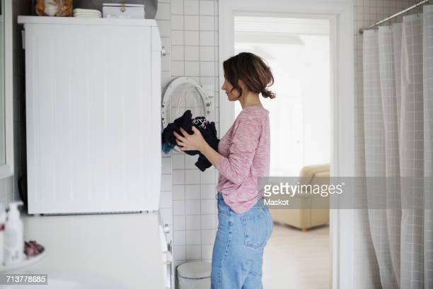side view of woman loading clothes in washing machine at home - washing stock pictures, royalty-free photos & images