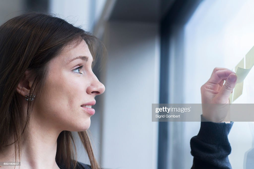 Side view of woman looking at adhesive notes stuck on window : Stock-Foto