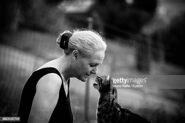 Side View Of Woman Looking At Cat On Field