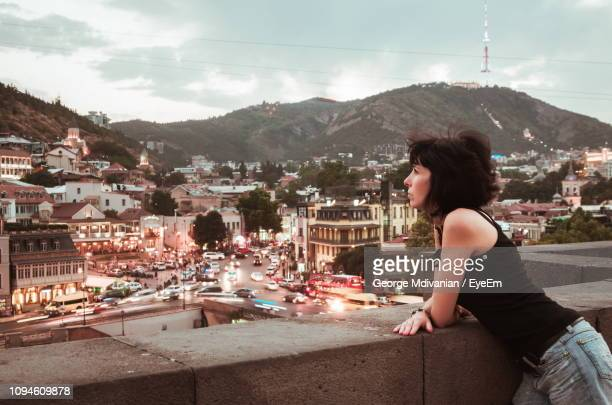 side view of woman looking at cityscape from observation point - トビリシ ストックフォトと画像