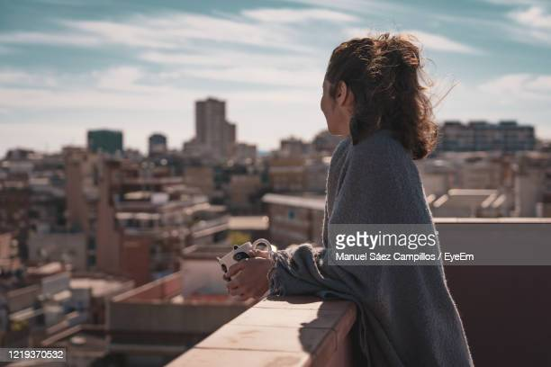 side view of woman looking at cityscape while standing on terrace - paisaje urbano fotografías e imágenes de stock