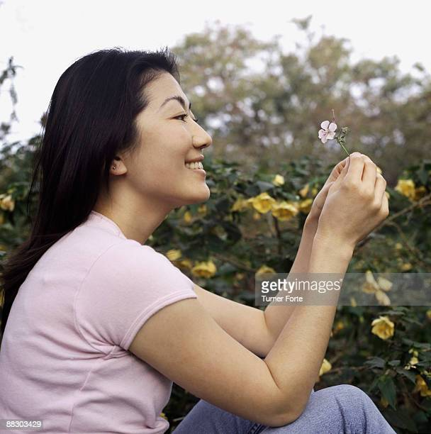Side view of woman looking at flower