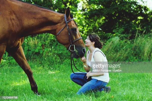 Side View Of Woman Looking At Horse On Field