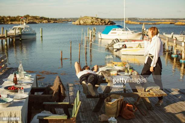 Side view of woman looking at man lying at harbor on sunny day