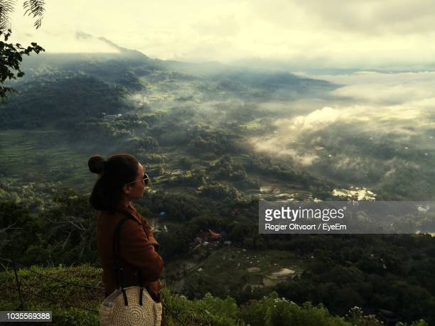 side view of woman looking at mountains - rantepao stock photos and pictures