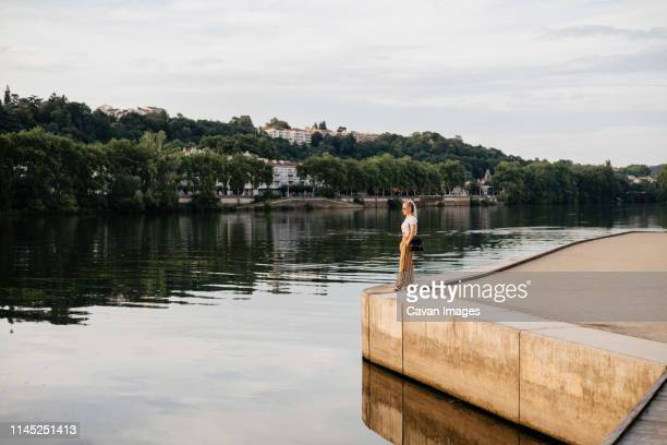 side view of woman looking at saone river while standing against cloudy sky during sunset in city - ローヌ県 ストックフォトと画像