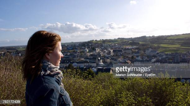 Side View Of Woman Looking At Townscape Against Sky