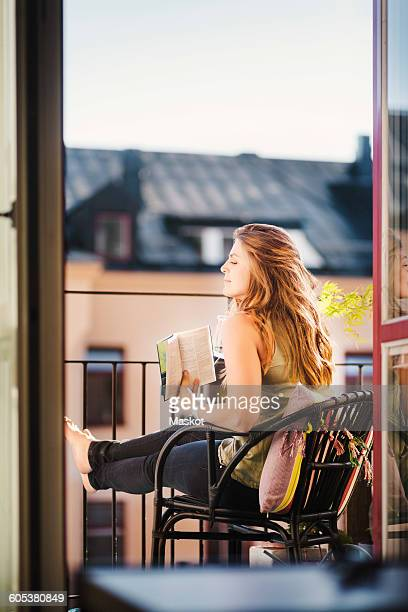Side view of woman looking away while holding guidebook at balcony
