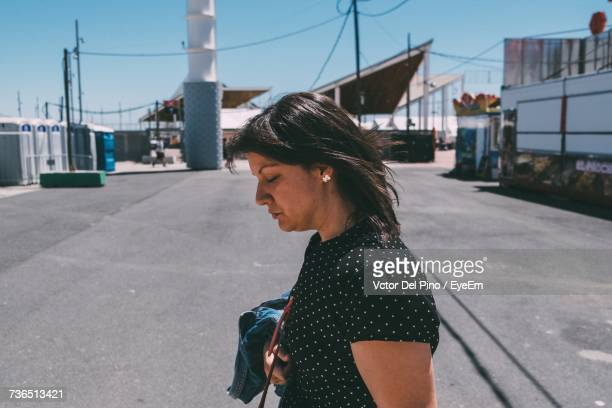 side view of woman looking down while standing on street - mid length hair stock pictures, royalty-free photos & images