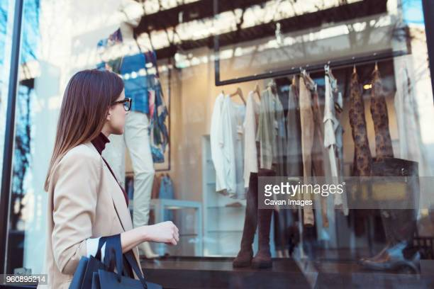 side view of woman looking in shop window while shopping in city - 欲望 ストックフォトと画像