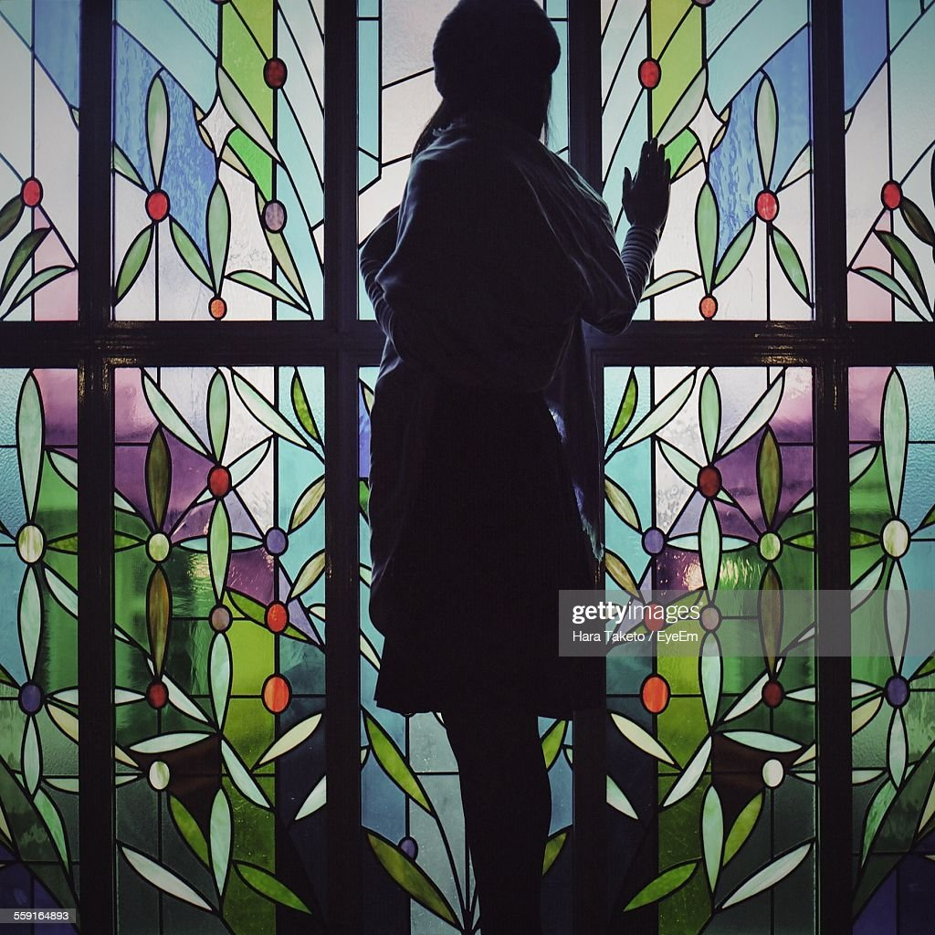 Side View Of Woman Looking Through Stained Glass : Stock Photo