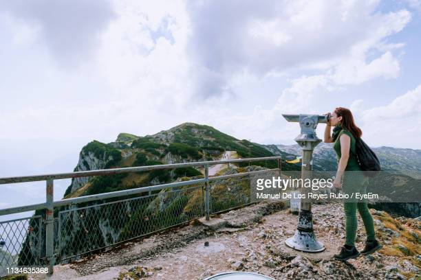 Side View Of Woman Looking Through Telescope While Standing On Mountain Against Sky