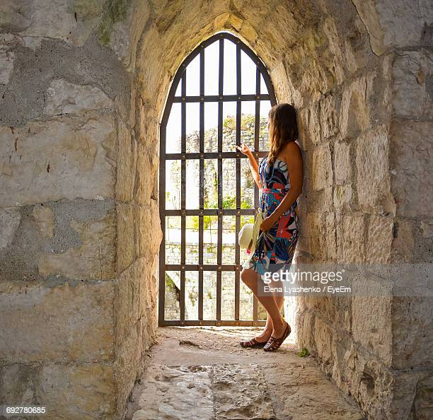Side View Of Woman Looking Through Window In Castle