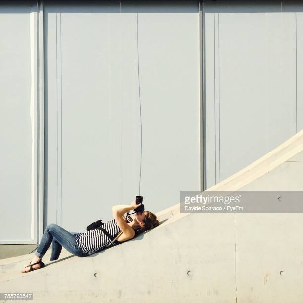 Side View Of Woman Lying On Retaining Wall While Photographing During Sunny Day