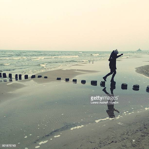 Side view of woman on stepping stones in sea
