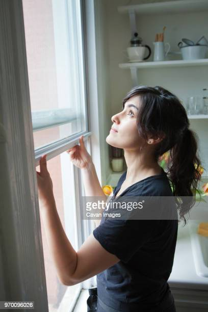 side view of woman opening window at home - window stock pictures, royalty-free photos & images