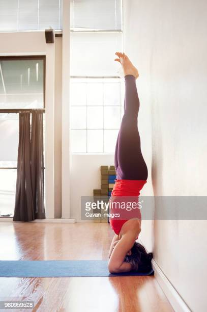 Side view of woman performing headstand at health club