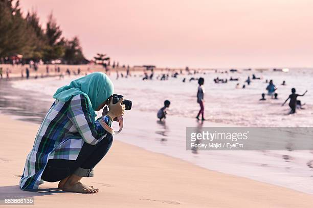 Side View Of Woman Photographing At Beach