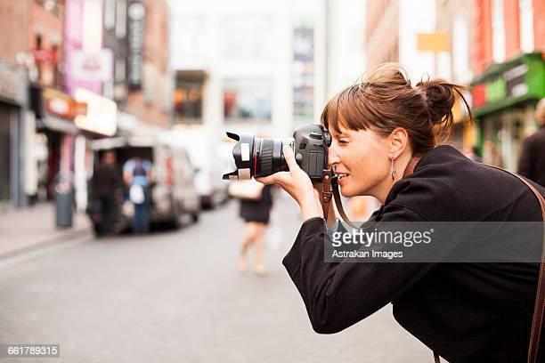 side view of woman photographing on city street - photographer stock pictures, royalty-free photos & images