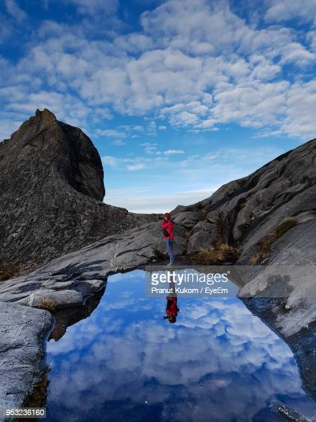 side view of woman photographing while standing on rock against sky - kota kinabalu stock pictures, royalty-free photos & images