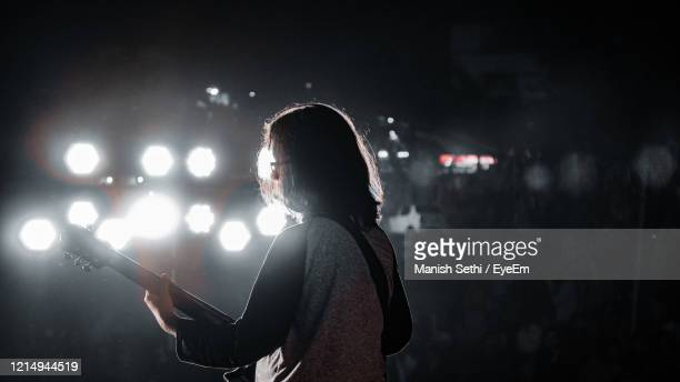 side view of woman playing guitar at night - guitarist stock pictures, royalty-free photos & images