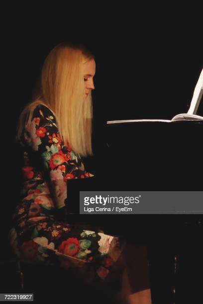 side view of woman playing piano in darkroom - liga cerina stock pictures, royalty-free photos & images