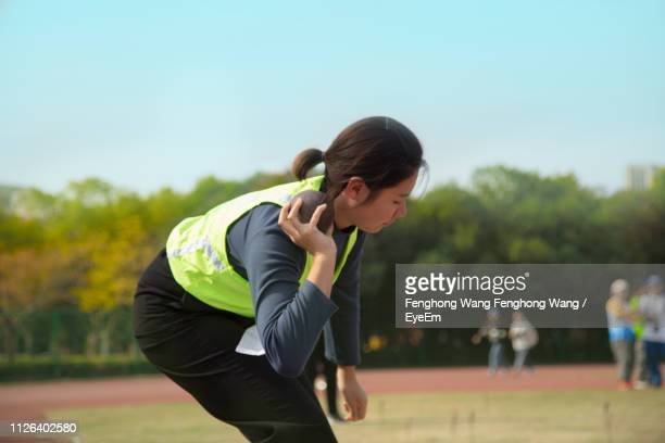 side view of woman playing shot put at park against sky - shot put stock pictures, royalty-free photos & images