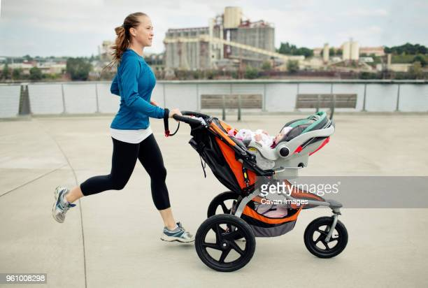 side view of woman pushing baby stroller while jogging in city - three wheeled pushchair stock pictures, royalty-free photos & images