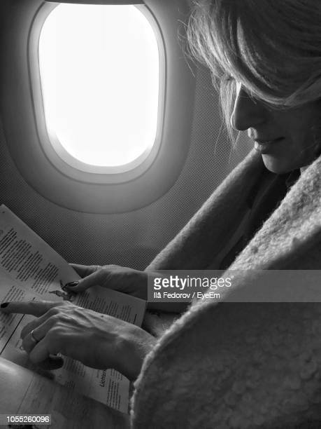 Side View Of Woman Reading Magazine In Airplane