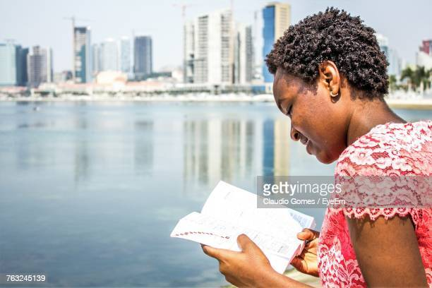 Side View Of Woman Reading Novel By Sea On Sunny Day