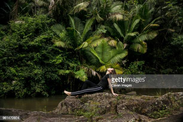 side view of woman relaxing on rocks at lakeshore in el yunque national forest - 頭をそらす ストックフォトと画像
